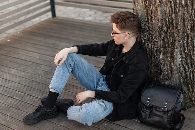 Elegante giovane piuttosto urbano in jeans alla moda vestiti in scarpe da ginnastica nere alla moda con zaino in pelle