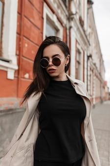 Elegante giovane donna piuttosto urbana in abito nero in trench alla moda primaverile giovanile in occhiali da sole alla moda a piedi vicino al muro vintage in strada. bella ragazza hipster in posa all'aperto in città. aspetto casual.