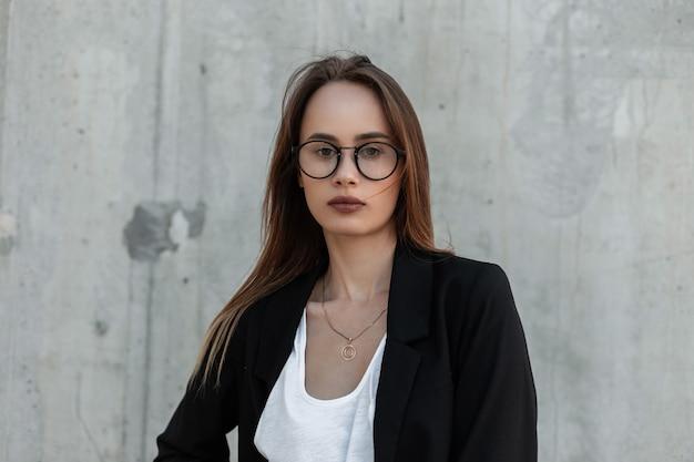 Elegante bella ragazza piuttosto giovane in abiti bianchi e neri di affari alla moda in occhiali classici di moda su sfondo grigio vintage su strada. vestito elegante alla moda per le donne. stile casual.