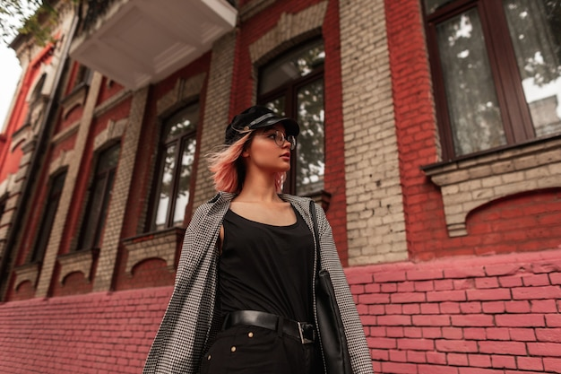 Elegante modello piuttosto giovane donna con occhiali alla moda e un cappello in abito casual con una t-shirt nera, camicia a quadri e jeans cammina per strada vicino a un edificio in mattoni rossi