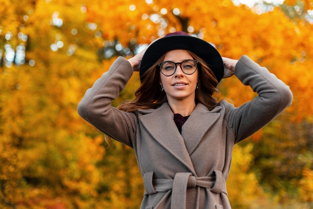 Elegante modello di moda donna abbastanza giovane raddrizza il cappello chic. attraente ragazza hipster piuttosto alla moda in cappotto elegante con gli occhiali pone nella sosta di autunno. abbigliamento femminile stagionale alla moda. stile.