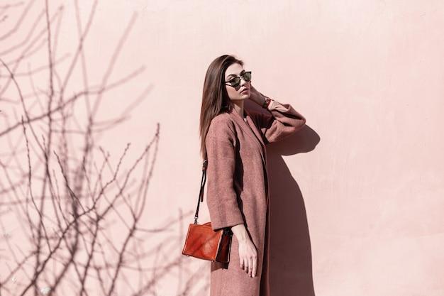 Elegante bella giovane donna con occhiali da sole alla moda in cappotto alla moda con borsetta alla moda in pelle si alza e gode del sole primaverile. modello adorabile della ragazza che riposa vicino alla parete d'annata sulla via il giorno soleggiato.