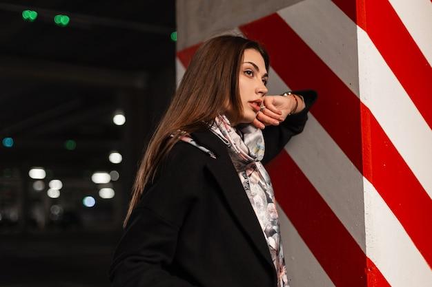 Elegante bella giovane donna in abiti eleganti della gioventù in posa sul parcheggio coperto. bella modella carina in cappotto nero con una sciarpa di seta vintage si trova vicino a una colonna con una linea rosso-bianca all'aperto.