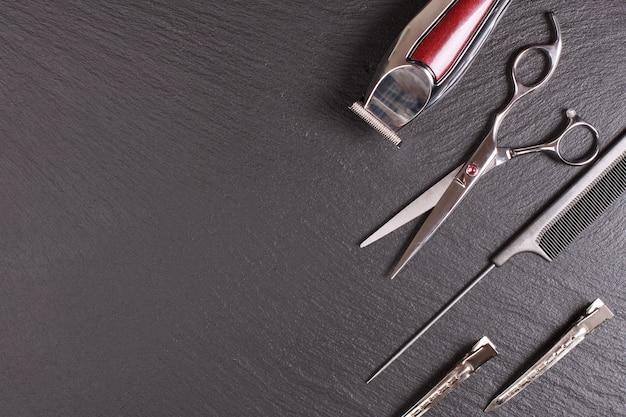 Elegante strumento professionale, taglio di capelli su sfondo nero. concetto di salone di parrucchiere, set per parrucchieri. accessori per il taglio di capelli. copia immagine dello spazio, vista dall'alto