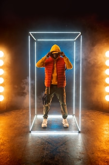 Il rapper alla moda posa in un cubo illuminato