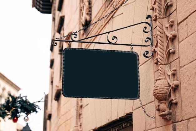 Elegante cartello bianco rettangolare in una cornice di ferro battuto è appeso al muro di pietra di un antico edificio
