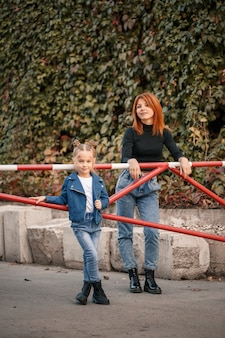La madre dai capelli rossi alla moda e sua figlia stanno parlando calorosamente. bambino felice e sua madre per strada. madre single di successo con sua figlia a fare una passeggiata. caloroso rapporto familiare
