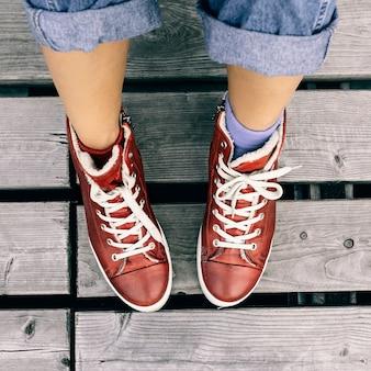 Scarpe da ginnastica rosse alla moda e vestiti di moda jeans. stile della città