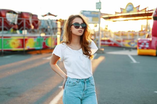 Giovane donna hipster moderna alla moda rossa in occhiali da sole alla moda in una maglietta bianca in jeans vintage in posa