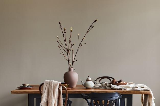 Interni rustici ed eleganti della sala da pranzo con tavolo in legno di noce, sedie retrò, decorazione, fiori secchi in vaso in un arredamento minimalista. modello. muro di fondo neutro.