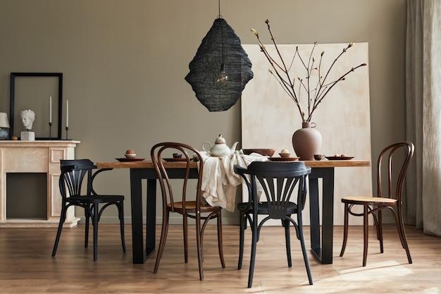 Interni rustici ed eleganti della sala da pranzo con tavolo in legno di noce, sedie retrò, decorazione, camino, fiori secchi, portacandele con cornice e tappeto in un arredamento minimalista. modello.