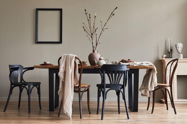 Interni rustici ed eleganti della sala da pranzo con tavolo in legno di noce, sedie retrò, decorazione, camino, fiori secchi, cornice portacandele e tappeto in un arredamento minimalista.