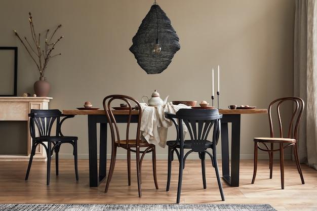 Interni rustici ed eleganti della sala da pranzo con tavolo in legno di noce, sedie retrò, lampada pedante, camino, fiori secchi, cornice portacandele e tappeto in un arredamento minimalista.