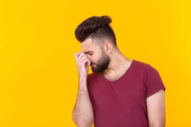 Elegante giovane pensieroso triste con la barba in una maglietta bordeaux in posa su una parete gialla