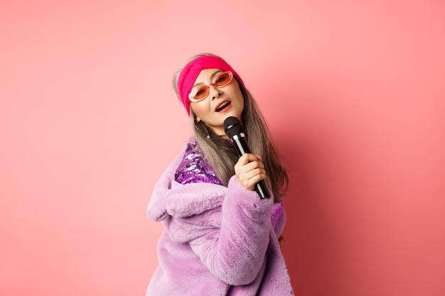 Elegante e sfacciata donna asiatica matura esegue una canzone sul palco, tenendo in mano il microfono e cantando al karaoke, indossando occhiali da sole a forma di cuore alla moda e cappotto di pelliccia sintetica, sfondo rosa