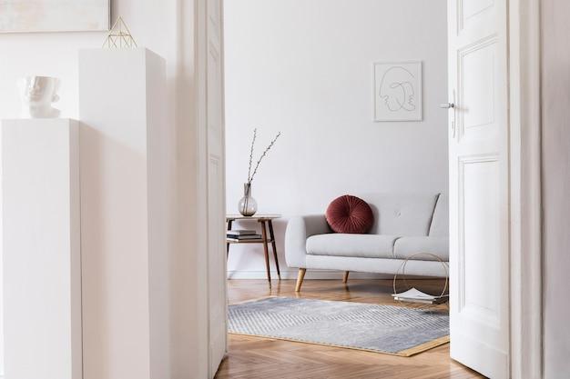 Interni eleganti scandi dello spazio domestico con divano grigio di design, tavolo in legno retrò, cornice per poster mock up, decorazione, moquette e accessori personali in un elegante arredamento per la casa.
