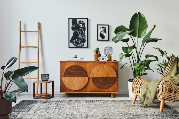 Elegante composizione scandinava di soggiorno con mobile di design, cornici nere per poster, poltrona, sgabello in legno, libro, decorazioni, piante e accessori personali