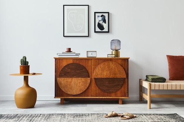 Elegante composizione scandinava di soggiorno con comò di design, cornici per poster finte nere, tavolo giallo, divano, libro, decorazione e accessori personali nell'arredamento moderno della casa
