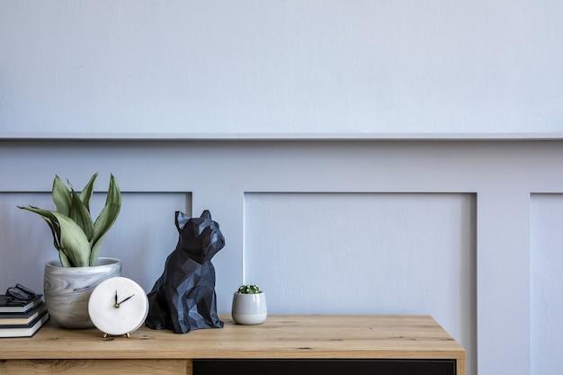 Elegante composizione scandinava con comò in legno, candela, succulenta in vaso, libri, orologio bianco, decorazione, spazio per copie e pannelli in legno grigio in un concetto moderno.