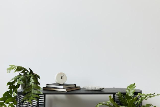 Interni eleganti per la casa scandinava con comò in legno di design, libri, decorazioni, spazio per le copie, piante ed eleganti accessori personali in un arredamento moderno. modello.
