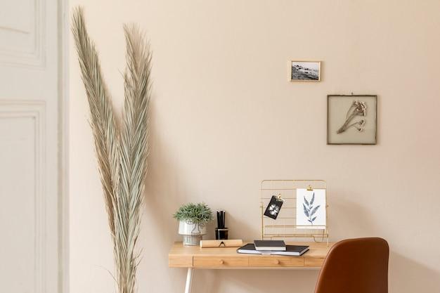 Eleganti interni scandinavi di uno spazio per l'home office con un sacco di cornici per foto finte, scrivania in legno, sedia marrone, piante, ufficio e accessori personali. home staging neutro moderno. modello.