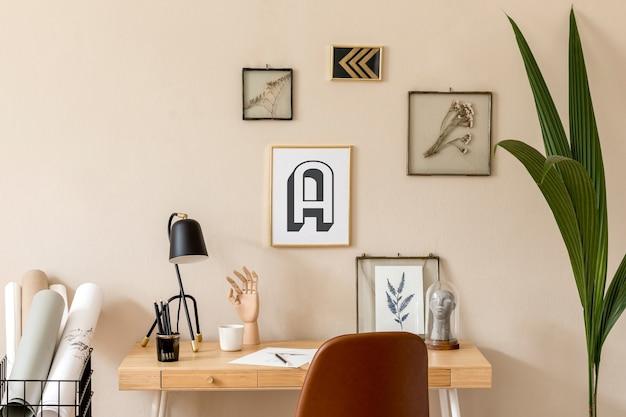 Interni scandinavi alla moda dello spazio dell'ufficio domestico con molte cornici per foto, scrivania in legno, sedia marrone, piante, ufficio e accessori personali. home staging neutro moderno.