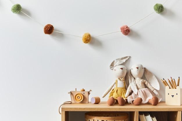 Elegante cameretta per neonati scandinava con giocattoli, animali di peluche, bambole e accessori per bambini. decorazione accogliente e batuffoli di cotone appesi alla parete bianca. copia spazio.