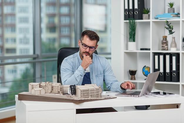 Elegante architetto senior lavora su un progetto di costruzione ed esamina i dettagli sul modello della futura casa.