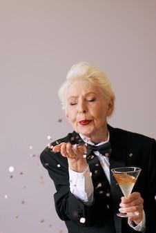 Elegante donna anziana in smoking con vetro con coriandoli che soffiano champagne per celebrare il nuovo anno Foto Premium
