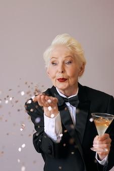 Elegante donna anziana in smoking con vetro con coriandoli che soffiano champagne per celebrare il nuovo anno