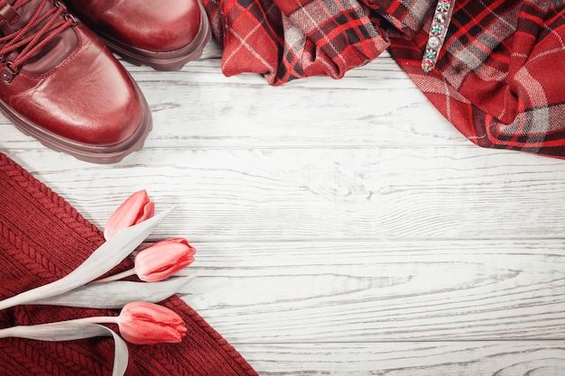 Vestiti di scarpe alla moda e tulipani di fiori di primavera su un fondo di legno grigio