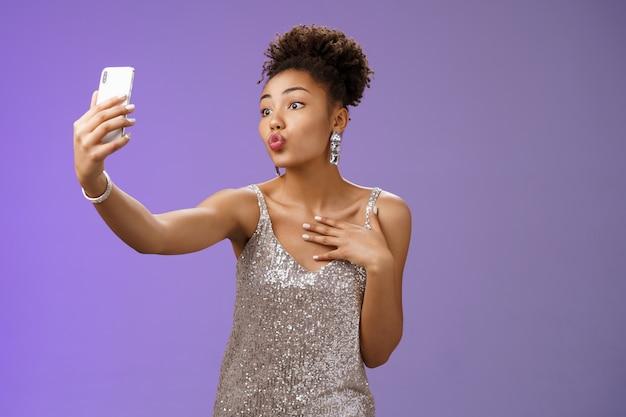 Elegante donna afro-americana femminile sciocca che fa festa in abito elegante argento piegando le labbra gesto di mwah in posa selfie prendendo foto durante il night club di festa alla ricerca di una telecamera con display civettuolo.