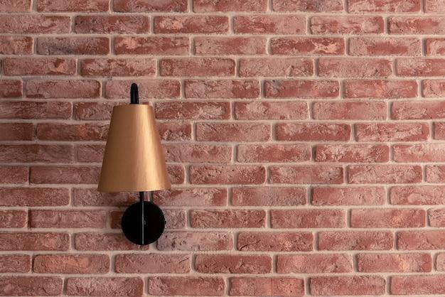 Elegante piccola lampada dorata applique installata sul muro di mattoni rossi contro la tenda della finestra marrone nel primo piano della camera appartamento contemporaneo. dettagli di interior design.