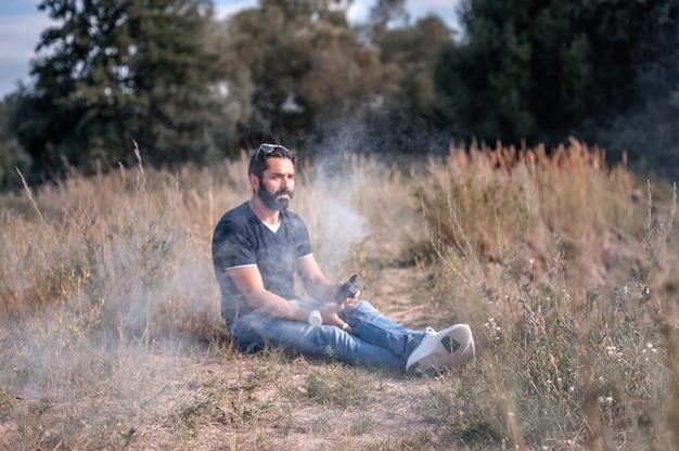 Il fumatore alla moda fuma la sigaretta elettronica espira il fumo nell'aria fresca