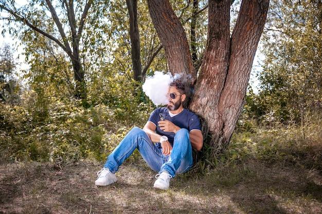 Fumatore alla moda con dispositivo di fumo elettronico all'aria aperta