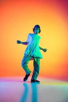 Elegante ragazzo sportivo che balla hip-hop in abiti eleganti su sfondo colorato