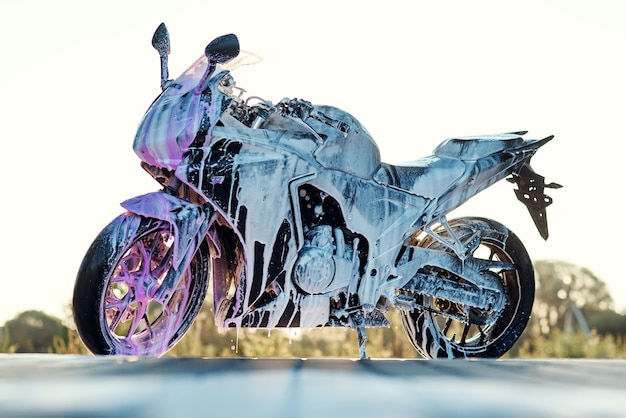 Elegante motocicletta sportiva con schiuma sull'autolavaggio self-service all'alba.