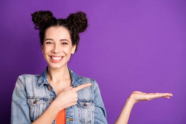 Elegante studente con capelli ricci in posa contro il muro viola