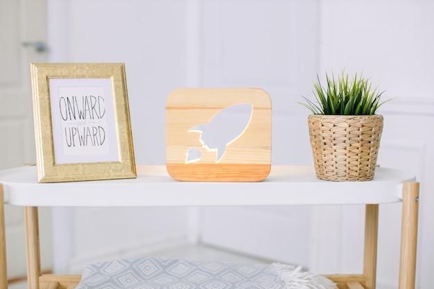 Tavolo elegante in soggiorno luminoso, con cornice per foto vintage, lampada decorativa in legno con immagine di razzo e pianta artificiale in vaso di fiori di vimini. arredamento e interni accoglienti.