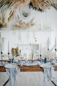Elegante tavolo con fiori secchi. piatto con forchetta e coltello dorati d'annata, candele, tovaglioli blu polverosi sulla tavola di legno. decorazione di nozze invernali.