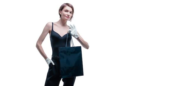 Elegante ragazza alta in guanti bianchi dimostra un pacchetto di lusso nero