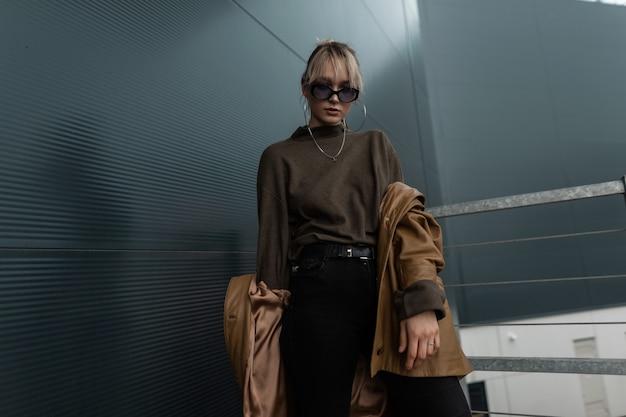 Elegante modello di ragazza carina adolescente con occhiali da sole alla moda in giacca marrone di pelle vintage con jeans neri vicino a un muro di metallo in città