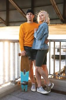 Una coppia di adolescenti alla moda ha un appuntamento sotto un ponte al tramonto