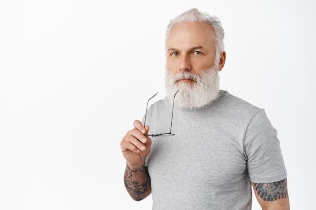 Elegante vecchio premuroso che tocca le labbra con la tempia degli occhiali, sembra serio davanti, pensa, riflette sulla decisione, in piedi con una maglietta grigia casual contro il muro bianco