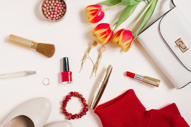 Elegante blogger piatto di tendenza. maglione rosso, orecchini, borsa, braccialetto, anello, rossetto, scarpe e cosmetici. vista dall'alto