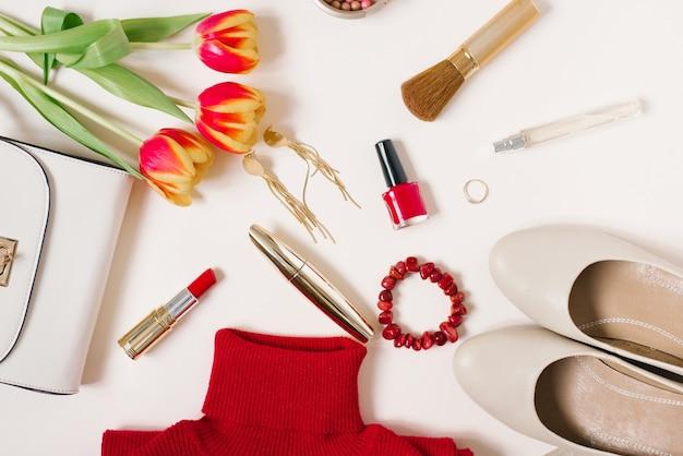 Elegante blogger piatto di tendenza per san valentino. maglione rosso, orecchini, borsa, braccialetto, anello, rossetto, scarpe e cosmetici. vista dall'alto