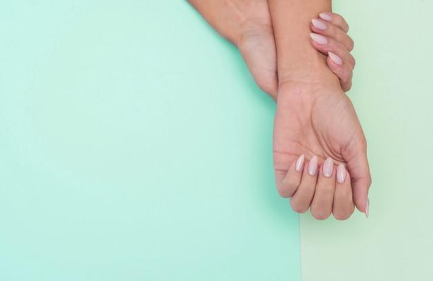 Manicure alla moda femminile alla moda. le mani della giovane e bella donna