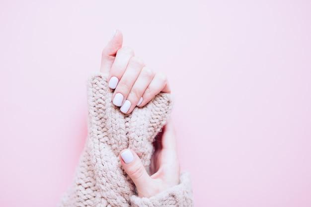 La giovane donna alla moda alla moda dell'unghia passa il manicure blu-chiaro su fondo rosa. manicure alla moda femminile alla moda. vista dall'alto. le mani della bella giovane donna su fondo rosa. copia spazio libero.
