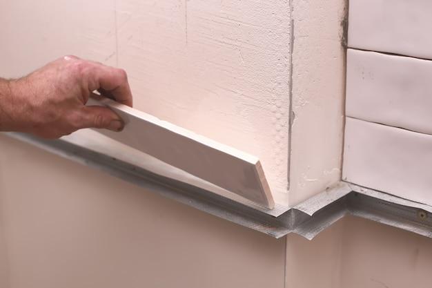 Piastrelle di ceramica bianche alla moda alla moda sulla parete della cucina. mani nel processo di posa di piastrelle rettangolari bianche sulla parete del bagno. ristrutturazione appartamenti e bagni. Foto Premium