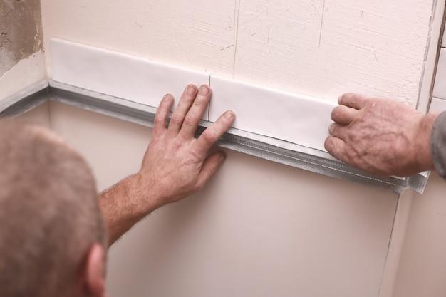 Piastrelle di ceramica bianche alla moda alla moda sulla parete della cucina. mani nel processo di posa di piastrelle rettangolari bianche sulla parete del bagno. ristrutturazione appartamenti e bagni.